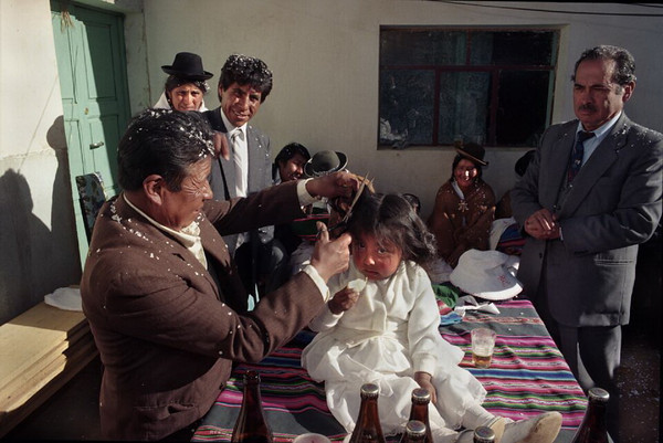 Rutuch'a in El Alto, 1995. A combination of Catholic and indigenous religious practices, the first haircut usually occurs after a child's baptism ceremony.  Alvaro and his immediate family invite extended family members and trusted friends to their home for food, celebration, and the rutuch'a (haircut).  In this photo, Alvaro and his wife, Silvia, watch as their neighbor Pablo wields the scissors to give their daughter her first trim.  The godfather, Don Jorge, conducts the ceremony, inviting guests to take a turn cutting the little girl's hair.  This responsibility is accompanied by a monetary gift to the girl's family to help provide for her future education or other needs.  Such participation and reciprocity between host and guest illustrates the strong relationship and mutual concern between the two parties.  A rutuch'a celebration is an opportunity for Alvaro and his wife to reaffirm their ties with family and friends.  They open their home and provide food, receiving financial assistance from those who most care for them.  The attendants are not necessarily neighbors, but rather those the family most trusts.  The placing of confetti in each other's hair identifies the celebrants and the importance of such bonds.  With the blessing of friends and family and a libation to the Pachamama, the fiesta will continue well into the night.